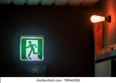 The emergency exit sign shows the direction of escape in case of danger. The emergency exit board over door in corridor inside the building.