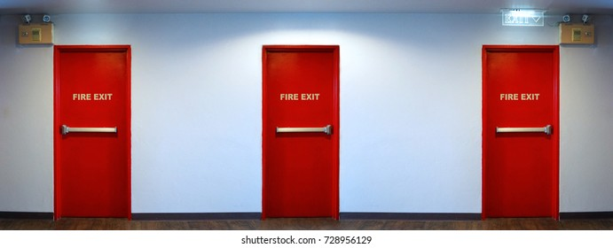 Emergency fire exit door red color metal material for safety protection and wood floor and white wall indoor building.
