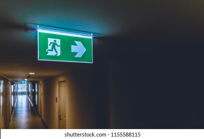Emergency fire exit green sign at the corridor in office building., close up at the signs.