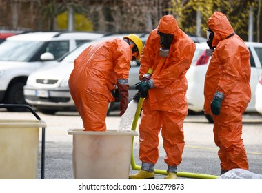 Emergency Firefighters at the scene of chemical accident with leakage of dangerous acid. Person with a orange protective suit against chemical and bacteriological agents it is washed.