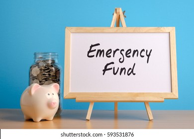 Emergency Fund, financial concept. Mason jar with coins inside, piggy bank and whiteboard on wooden table.