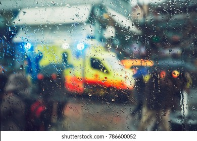 Emergency medical service response in the city. Ambulance cars on the rush street during rain. View through a car window and selective focus on the raindrop. Prague, Czech Republic.