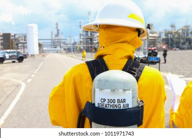 An emergency response personnel in yellow coverall wearing a compressed air tank for rescue in a petrochemical plant.