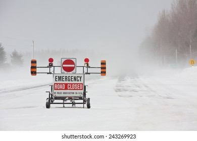 An emergency road closed barrier on the highway during a blizzard.