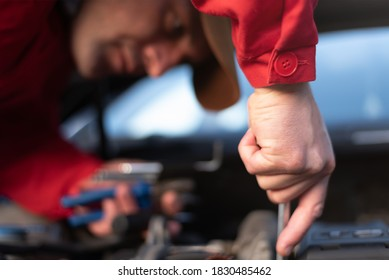 Emergency roadside assistance, road assistance worker in uniform trying to fix car breakdown or engine failure.  Roadside assistance concept