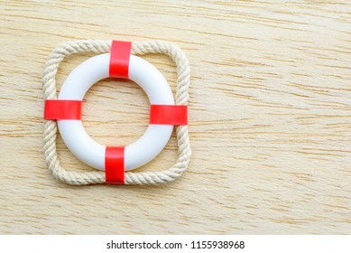 Emergency service, rescue / fast first aid concept : Top view red lifebuoy / lifebelt on wood background, depict the time of emergency that need an extreme responsive or quick rescue using lifesaver