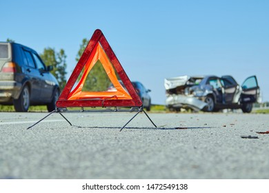 emergency sign on the highway at the scene of an accident and damaged car on background