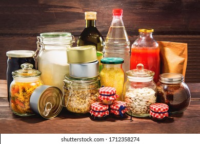 Emergency stockpiling of various food, on top of wooden background.