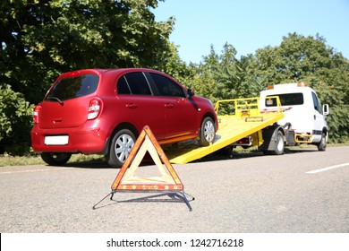 Emergency stop sign with broken car and tow truck on background