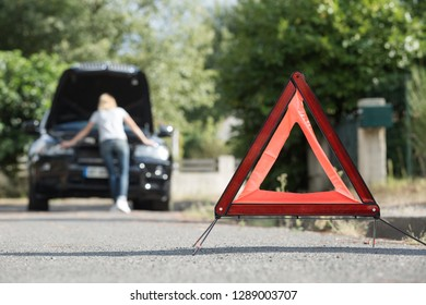 emergency stop sign and broken car on the road