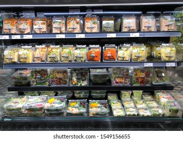 Emeryville, CA - Oct 31, 2019: Grocery store refrigerator aisle with containers of pre-packaged wraps and salads, ready to go for lunches and dinners. Cheaper than fast food alternatives.