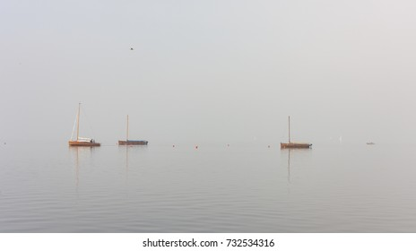 Emigration boats and other boats in a special light mood with fog on Lake Steinhude