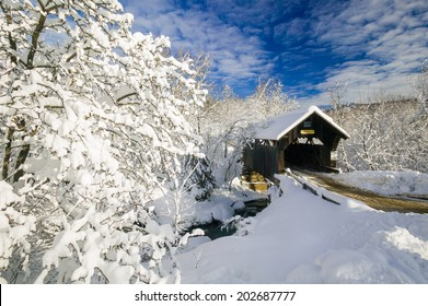 Emily's Covered Bridge blanketed in fresh snow on a sunny winter morning, Stowe, Vermont, USA