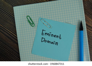 Eminent Domain write on sticky notes isolated on Wooden Table.