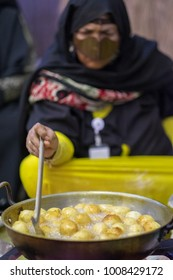 emirate lady cooking luqaimat sweet in Sweehan Heritage Festival February 13, 2015 in Abu Dhabi, United Arab Emirates
