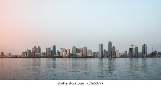 The Emirate Of Sharjah. Evening landscape of the city promenade with walking people and architecture.