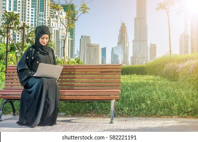 Emirates Business. Arab businesswomen in hijab working at a laptop on the background of skyscrapers of Dubai. The woman is dressed in a black abaya