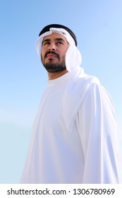 Emirati Arab man wearing traditional UAE kandora garment on isolated sky background