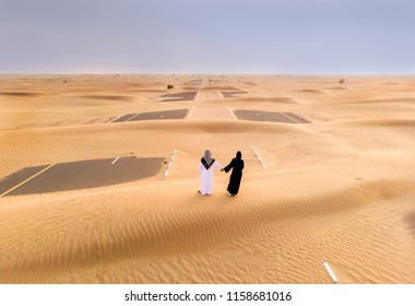 emirati couple in a desert looking at a sand covered road