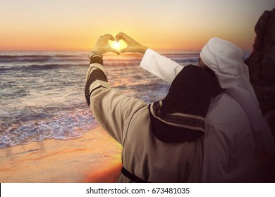 Emirati couple romantic in love at beach sunset. happy young couple making heart sahpe with hand on the beach during travel holidays vacation