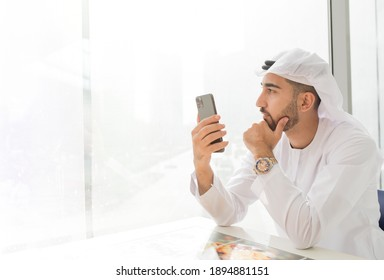 Emirati entrepreneur in UAE traditional outfit holding a mobile phone and looking out through the glass window. Arabic ambitious mature business man.