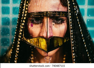 Emirati Middle Eastern woman's face cover with burka under the shower with ink on face