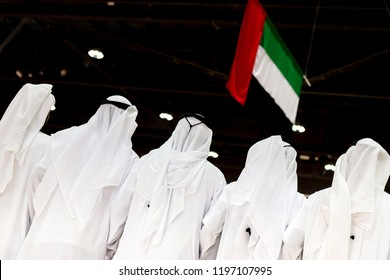 Emirati unrecognisable men looking at the UAE flag, concept of patriotism and celebration of the national day