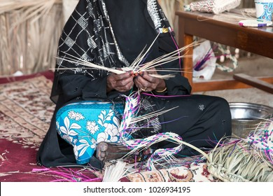 Emirati woman is making traditional basket by weaving from palm leaves