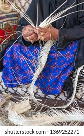 Emirati woman is weaving traditional basket from palm leaves, hands in frame