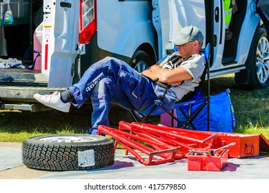 Emmaboda, Sweden - May 7, 2016: 41st South Swedish Rally in service depot. Crew person taking a nap before the cars arrive from the track. New tire and support stands beside him.