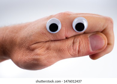 Emoji. A face made from a hand shows doubt. Emoji icon doubter. A hand with plastic eyes shows emotions. The person expresses doubt. Doubting face. Smiley - person without emotions. Smileys Neutrality