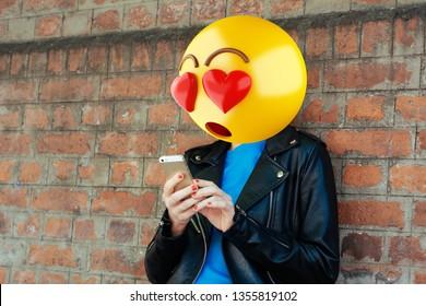 Emoji head woman using a smartphone. Emoji concept