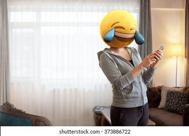 Emoji Head Woman. Woman wearing tears of joy emoji masks while looking at her phone. This emoji is laughing so much that it is crying tears of joy