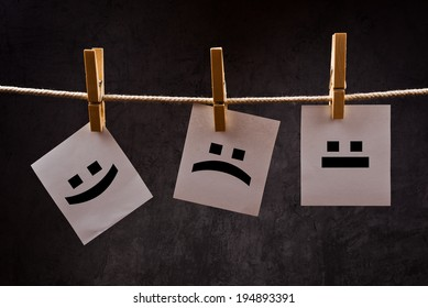 Emoticons printed on note paper attached to rope with clothes pins - happy, sad and neutral.