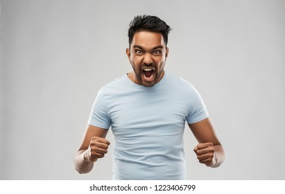 emotion, anger and people concept - angry indian man screaming over grey background