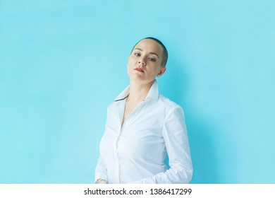 Emotion of arrogance, superiority, arrogance. Portrait confident beautiful happy young bald woman in white shirt on colored background wall. Human emotions facial expression concept Success