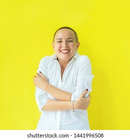 Emotion of direct joy and surprise and hug herself. Portrait confident beautiful happy young bald woman in white shirt on colored background wall. Human emotions facial expression concept Success