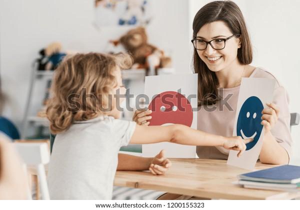 Emoción emoticonos utilizados por un psicólogo durante una sesión de terapia con un niño con un trastorno del espectro autista.