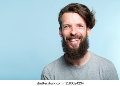 emotion expression. very happy joyful thrilled to bits man with beaming smile. young handsome bearded guy portrait on blue background.