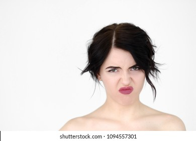 emotion face. bad smell and stinky rancid odour disgust concept. young beautiful brunette girl portrait on white background.