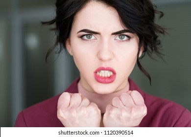 emotion face. furious angry woman in rage baring the teeth. young beautiful brunette girl portrait