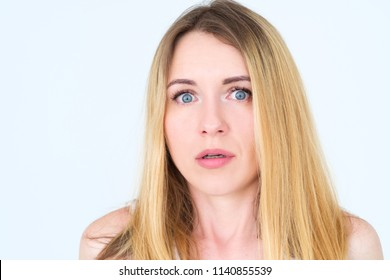 emotion face. overwhelmed perplexed shocked surprised astounded woman young beautiful blond girl portrait on white background.