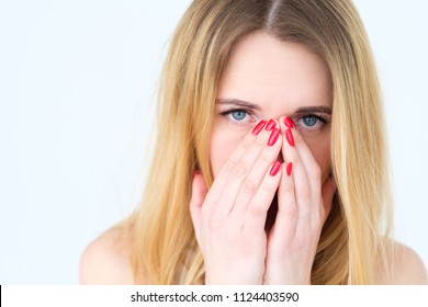 emotion face. sad upset woman covering her face with hands. young beautiful blond girl portrait on white background.
