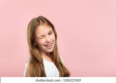 emotion face. smiling cute adolescent girl pleased with herself. young pretty brown haired kid winking. portrait on pink background.