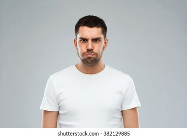 emotion, fun and people concept - man with funny angry face over gray background