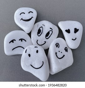 Emotion management concept, stones with painted faces symbolize different emotions. We are all different, but all together, learning to manage emotions. Grey background, white stones. - Shutterstock ID 1936482820