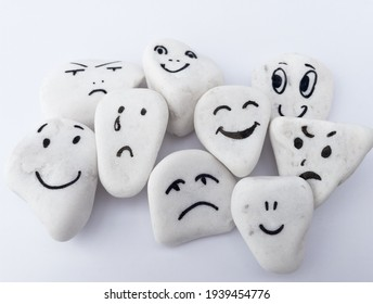 Emotion management concept, stones with painted faces symbolize different emotions. We are all different, but all together, learning to manage emotions. Soft background, white stones. - Shutterstock ID 1939454776