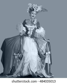 Emotion woman in a dress style of the 18th century with a yellow fan on gray background