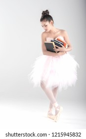 Emotion work is dance,education woman in pink ballet dance stand on floor,hand hold colorful thick book.