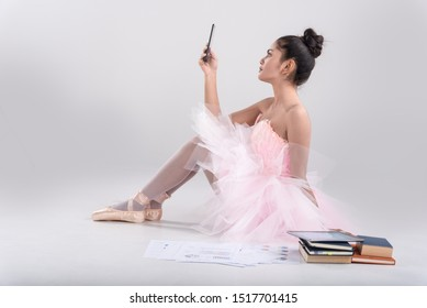 Emotion work is dance.Happy business,education asian woman in ballet dance style.sit on floor,hand hold hand phone,colorful thick book ,and business graph put near her.